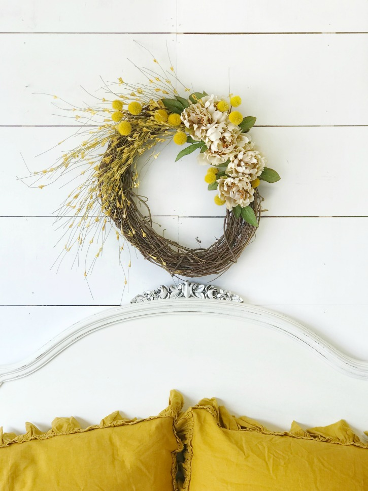 fall wreath above white headboard and 2 yellow pillows