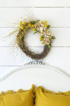How to Make a Fall Wreath for Your Home wreath above white headboard and 2 yellow linen pillows