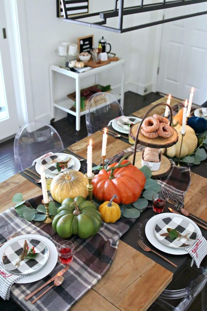 table with 3 large pumpkins plaid table runner and 6 candles