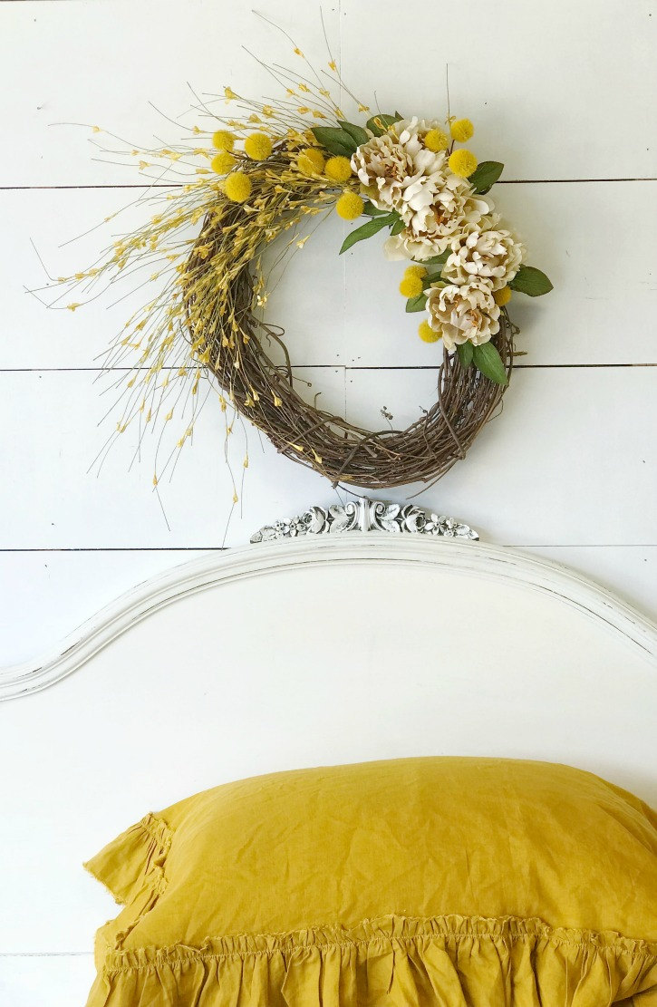 How to Make a Fall Wreath for Your Home with wreath aove white headboard and 2 yellow linen pillows stacked