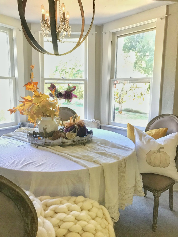 dining room fall table with pumpkin pillow and white table cloth with leave centerpiece