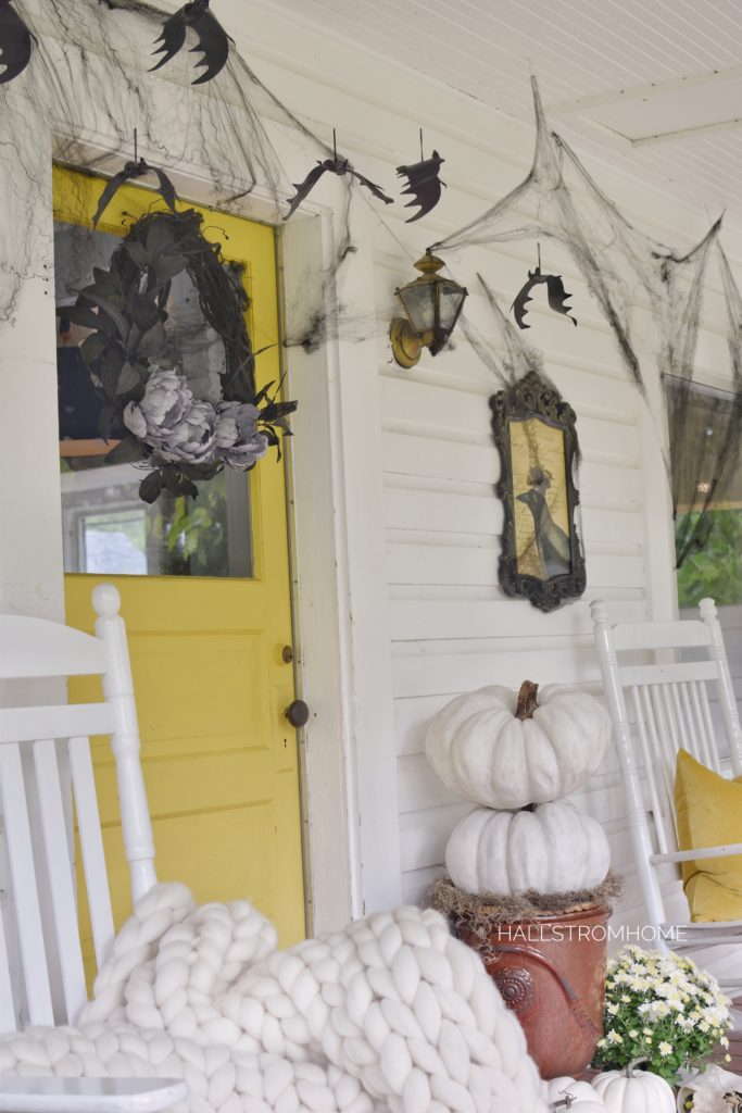 yellow door with black wreath and black webs around door with bat hanging and a stack of white pumpkins