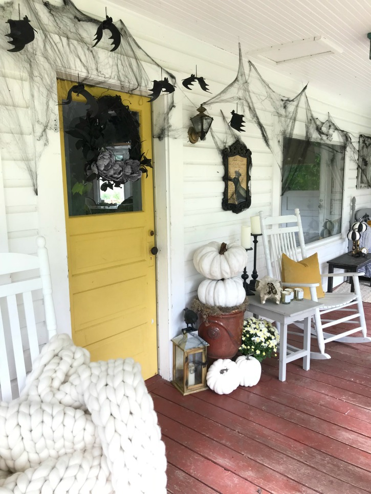 Simple, Easy Halloween Porch Decorating You Can Actually Do with yellow door and black wreath with white stack of pumpkins and bats hanging around