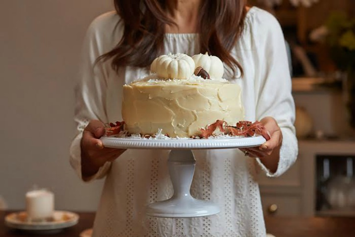 Happy Happy Nester Holding white pumpkin cake on white cake platter