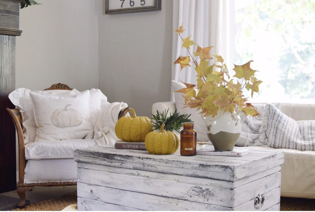 Beautiful Fall Farmhouse Home Tour with Easy Scone Recipe with white trunk with 2 pumpkins vase and candle on top