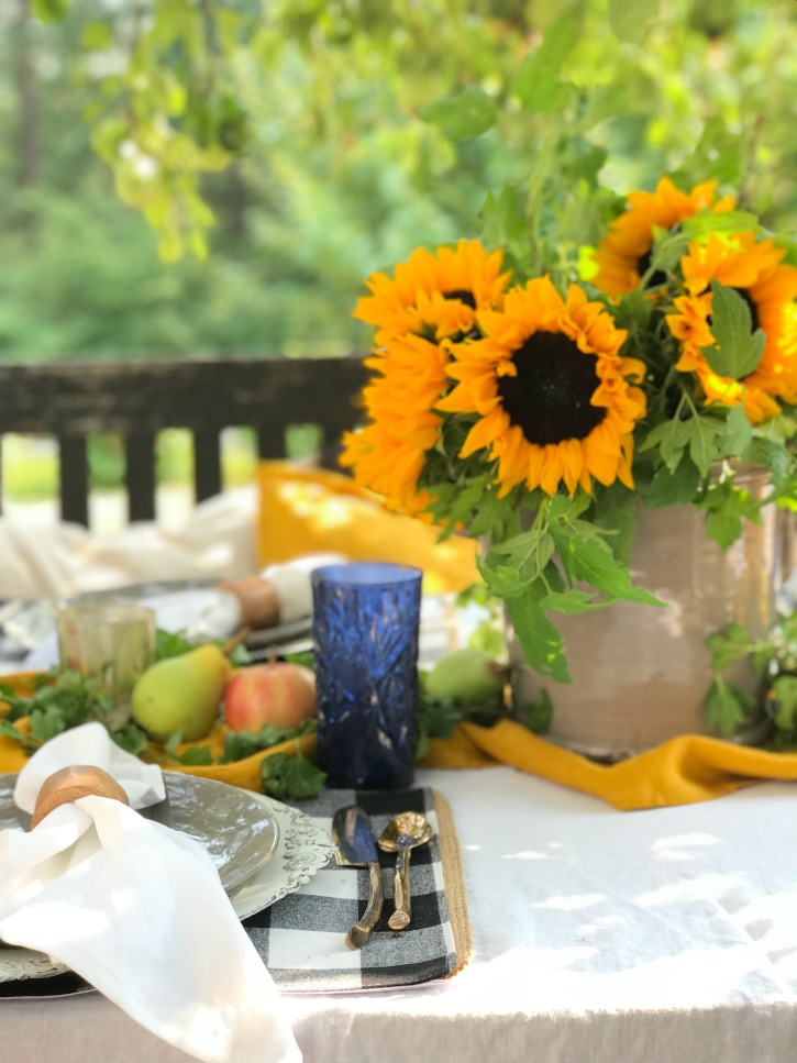 grey plate with gold silverware and bouquet of sunflowers