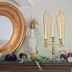 How to Style Beautiful Velvet Pumpkins on a Fall Farmhouse Mantel with 5 pumpkins and angel wings hanging with gold round mirror