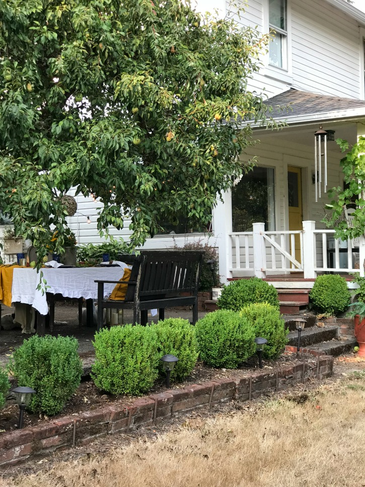 white farmhouse with 5 bushes and table outside