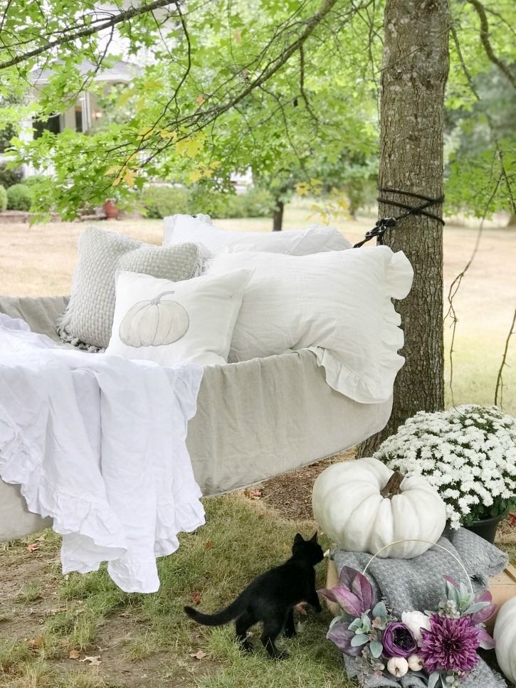 hammock filled with white linens and pumpkin pillow with pumpkins and mums on ground