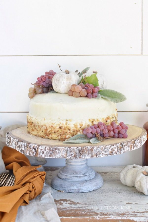 How to Make the Best Pumpkin Spice Cake with Cream Cheese Frosting with white cake and clumps of grapes and 3 white pumpkins on top