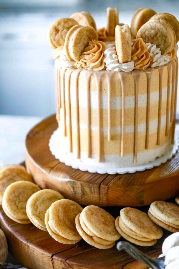 19 of the Best Pumpkin Fall Recipes with orange and white cake with dripped sides and cookie sandwiches on top with dollops of icing