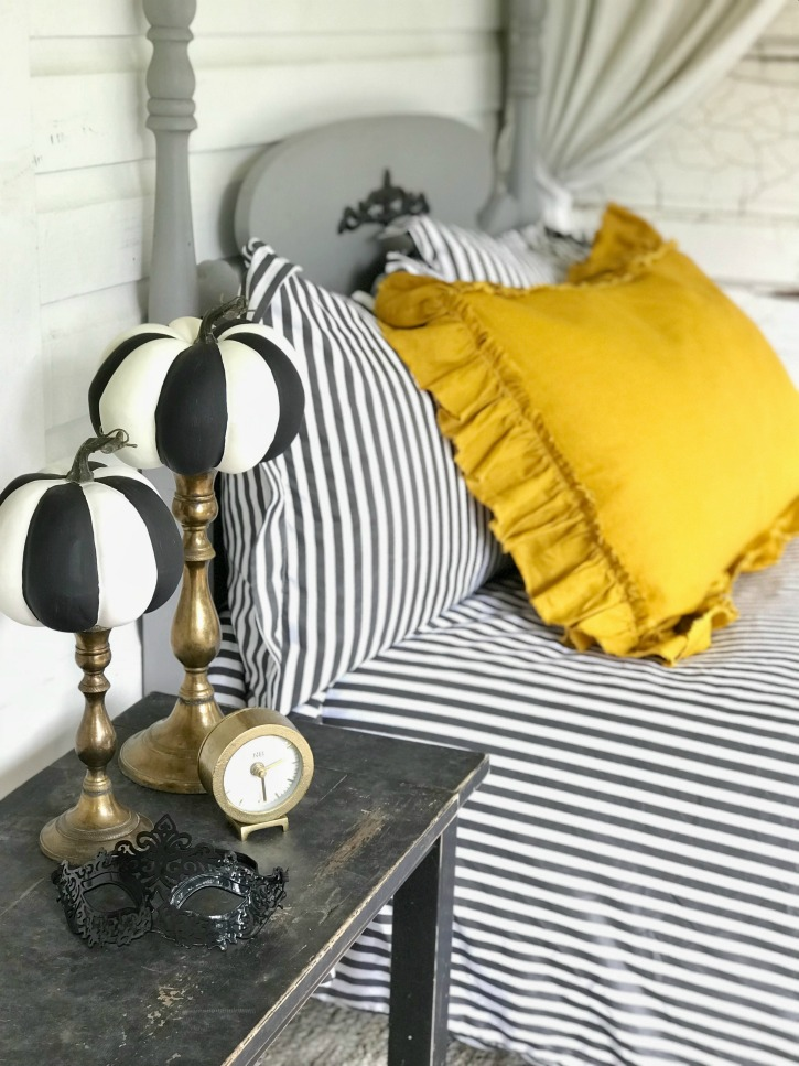 yellow and striped bedding with gold candle holdesr with striped pumpkins on top