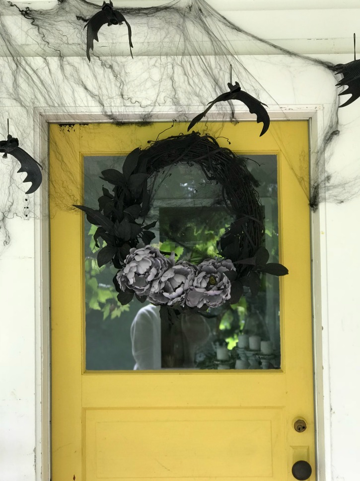 yellow door with black wreath and purple rose and cobwebs with bats