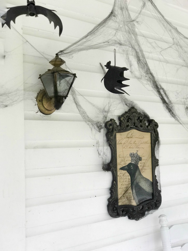 black frame with crow print and cobwebs with bats hanging