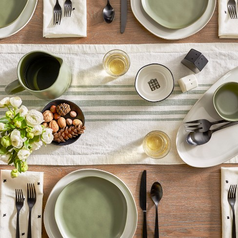 Magnolia Home with green and white table runner and green plates on top of white with black silverware