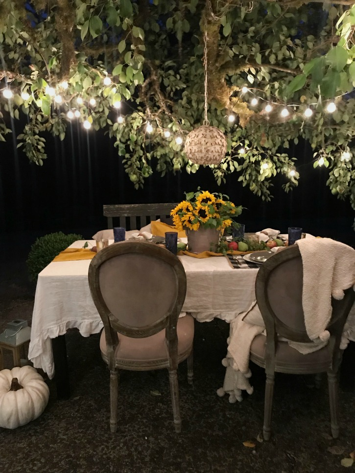 outdoor table with white linen tablecloth and bouquet of sunflowers with round chandelier