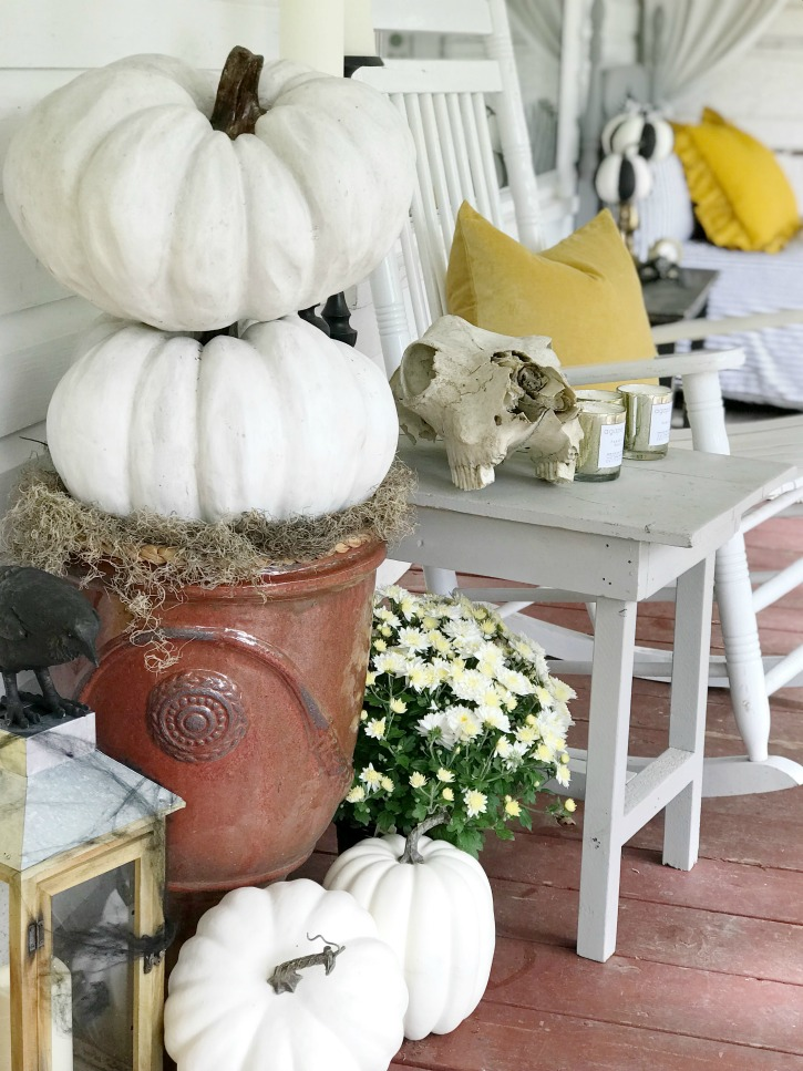 2 white pumpkins stacked with 3 on the ground and lantern with crow on it