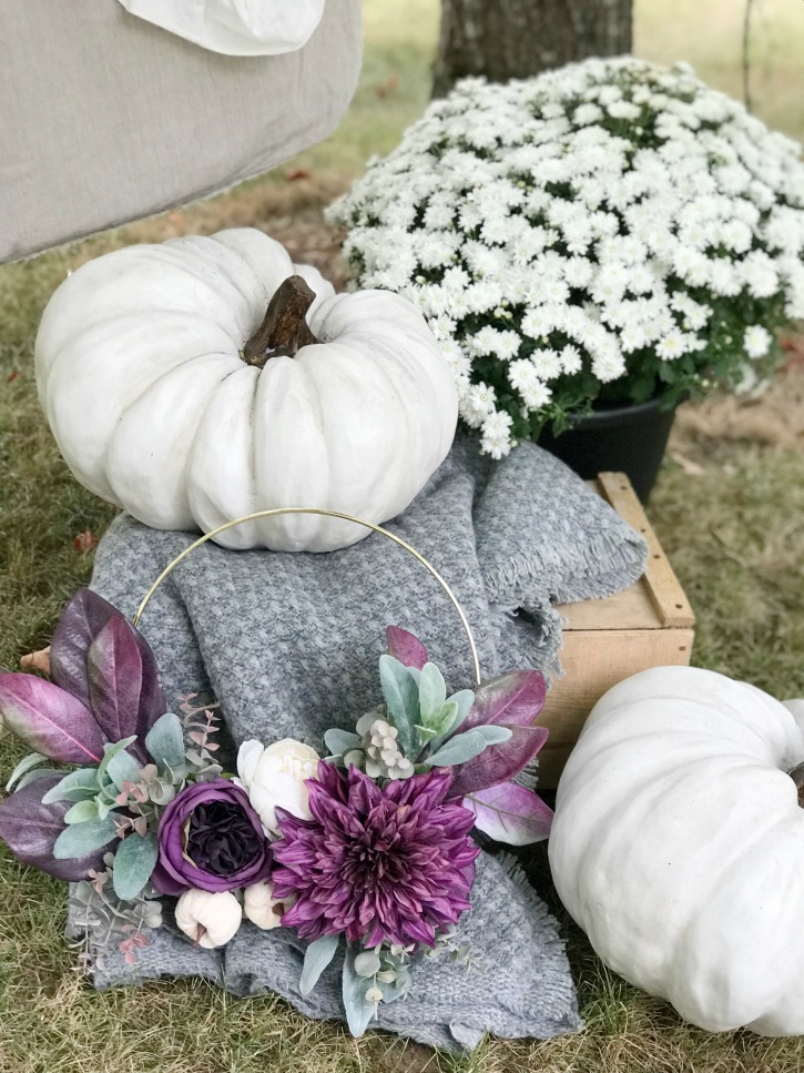 2 white pumpkins on crate with purple wreath and grey blanket with white mum