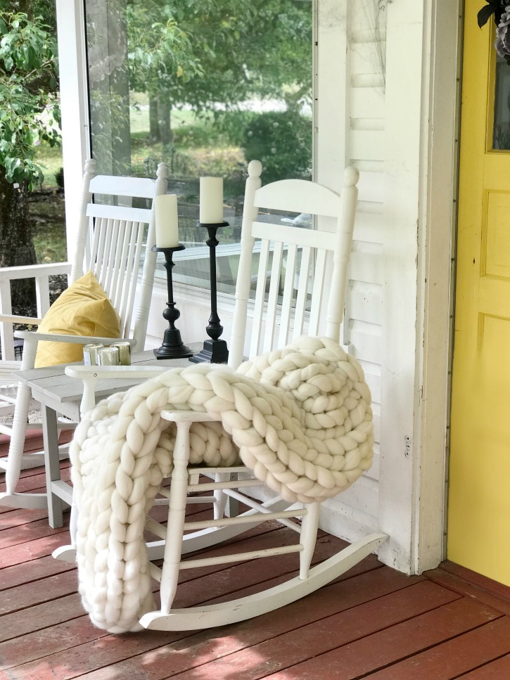 yellow door with 3 white rocking chairs on porch with hanging bats and cobwebs wiht pumpkins and whte chunky blanket on one rocking chair