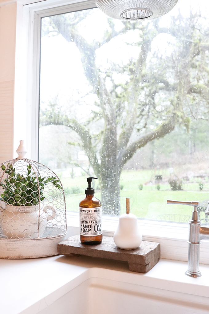 9 Kitchen Sink Style Tips |Farmhouse Kitchen sink|farmhouse style|farmhouse kitchen|white farmhouse|style kitchen|how to style kitchen|white kitchen|modern white kitchen|gold kitchen|shabby chic kitchen|kitchen update|kitchen remodel|kitchen sink|style a kitchen sink|charcuterie board|wood board|white pear|wood pedestal|wood tray|mango wood| Hallstrom Home